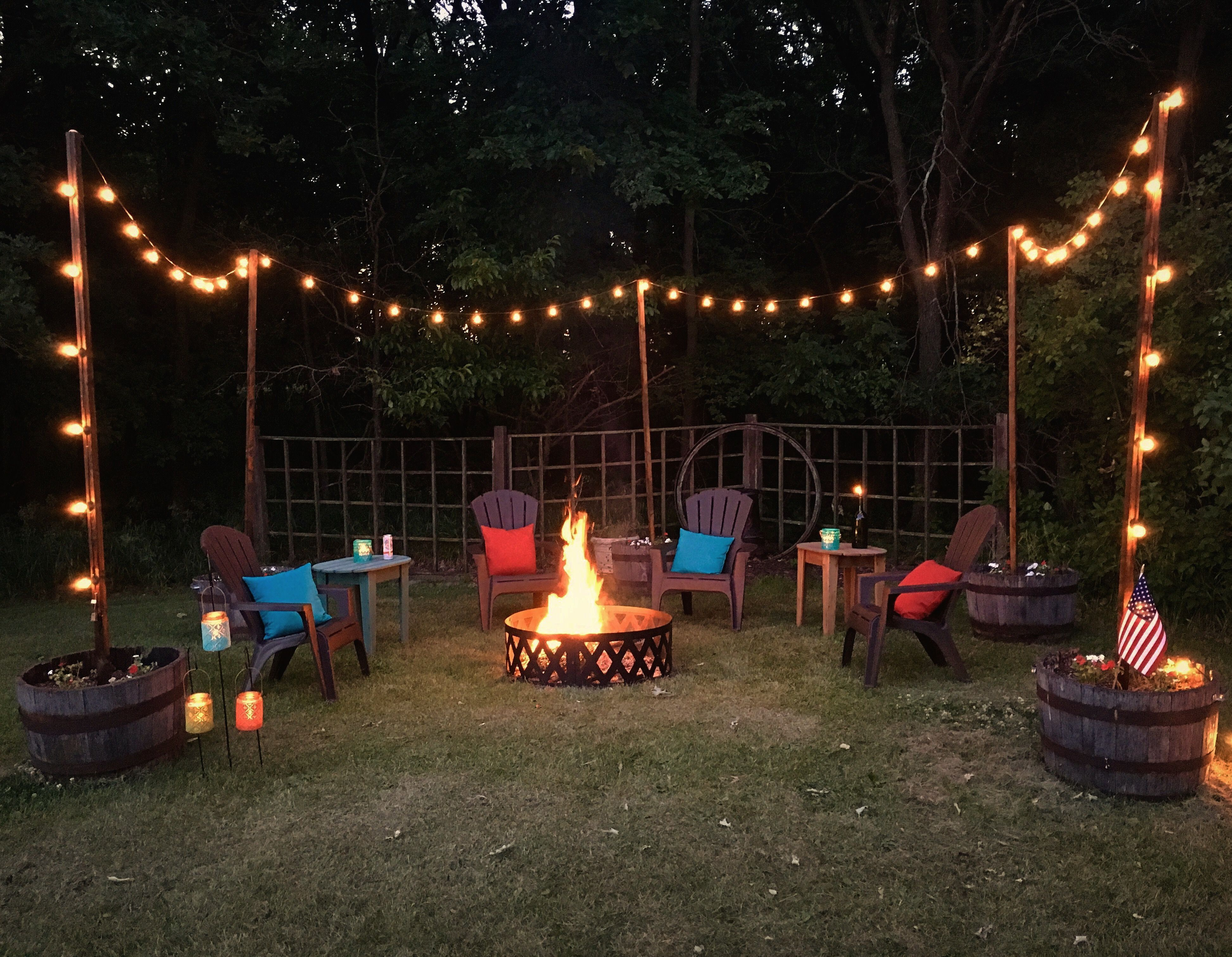 Photo of Outdoor living space with seating and fire pit. String lights on poles , whiskey…