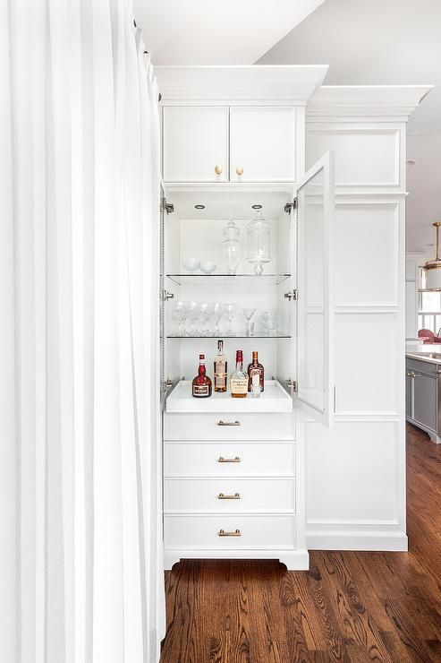 A Tall White Bar Cabinet Is Fitted With White Shelves Adorned With