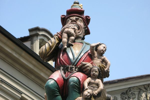 """Standing in the middle of Bern, Switzerland, is the Kindlifresser, or """"Child Eater."""" The fountain sculpture towers above the ground a baby half stuffed into his mouth, and a sack full of three alarmed tots slung over its shoulder presumably for later snacking. The disturbing sculpture is no modern work of art; built in 1546, it is one of the oldest fountains in the city of Bern."""