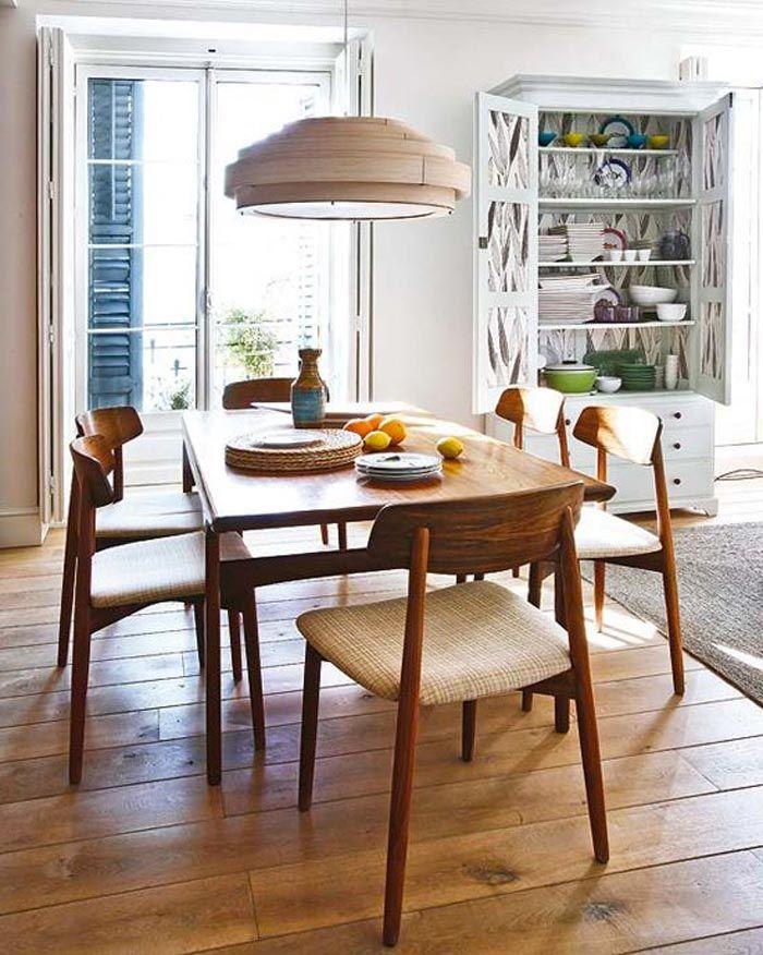 En el comedor: mesas de madera y sillas con respaldos envolventes ...
