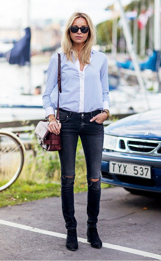 45d1ca357e0 A blue and white striped button-down shirt is paired with distressed skinny  jeans