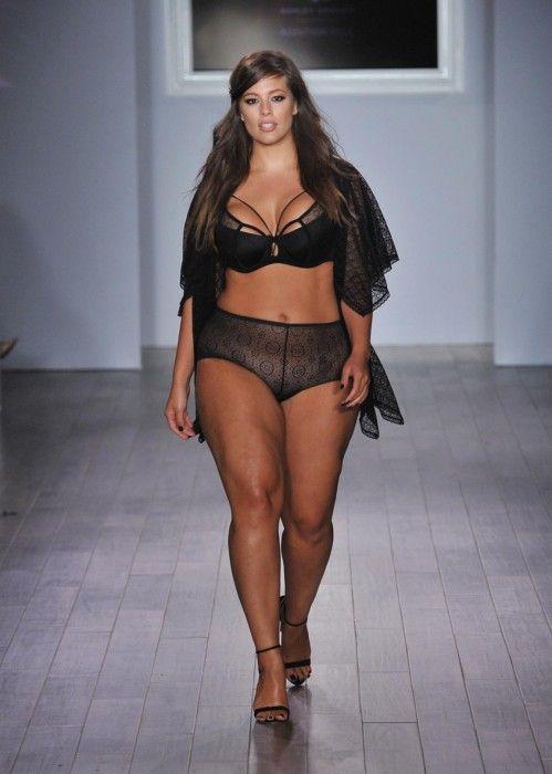 f35c6c2d2fe0 Modelo de tallas grandes caminado por la pasarela con ropa interior de  encaje color morado y una bata de color negro