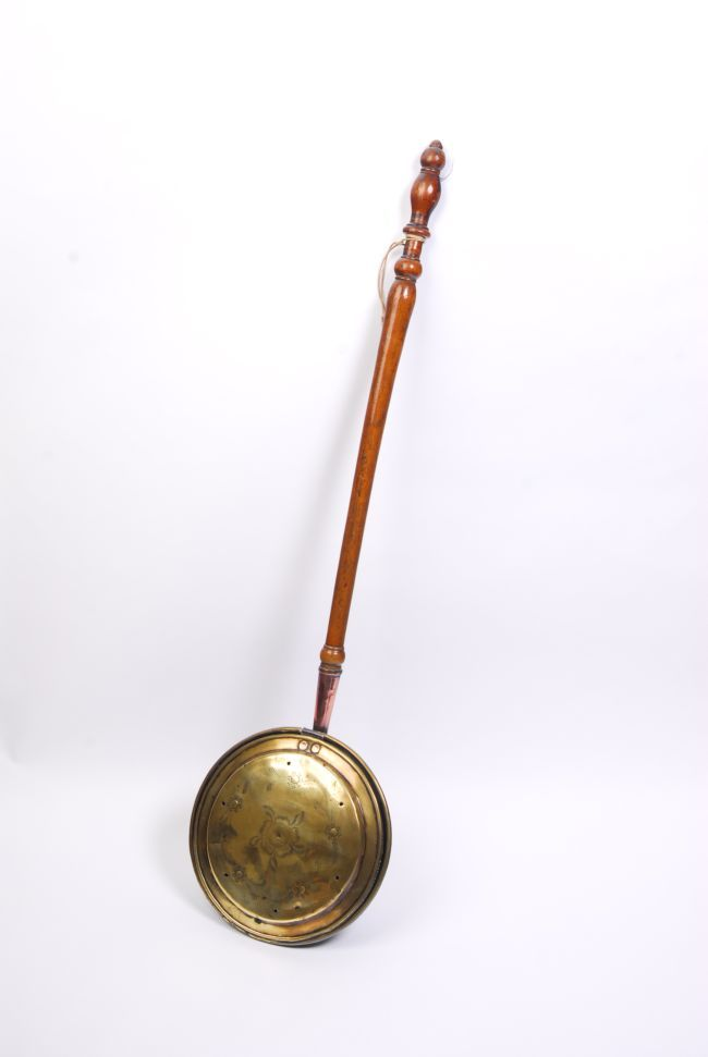 a victorian brass bed warming pan, filled with hot coals and place ...