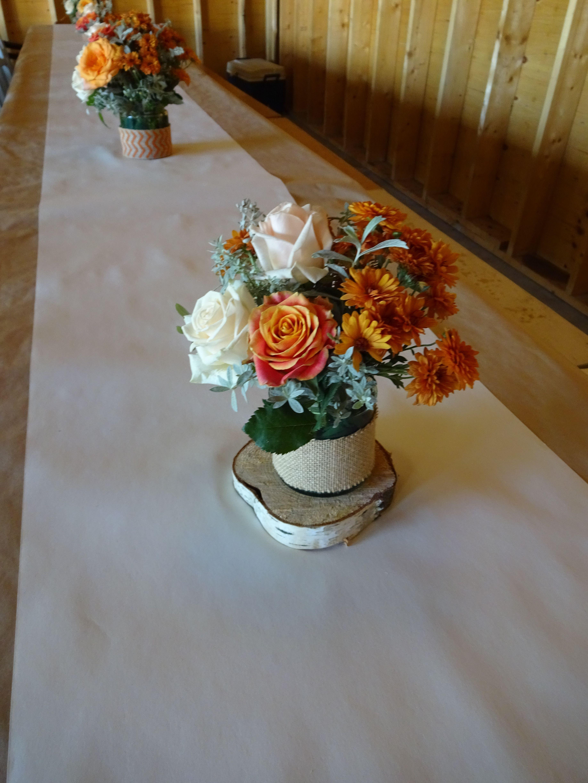 centre de table de fleurs orange, beige et gris, sur tranche de bois