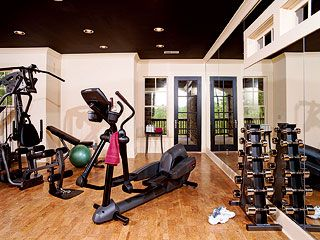 the workout room has hardwood floors and one of the walls