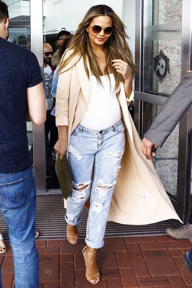 Chrissy Teigen wears a wrap coat over a white bodysuit with distressed jeans  and Stuart Weitzman