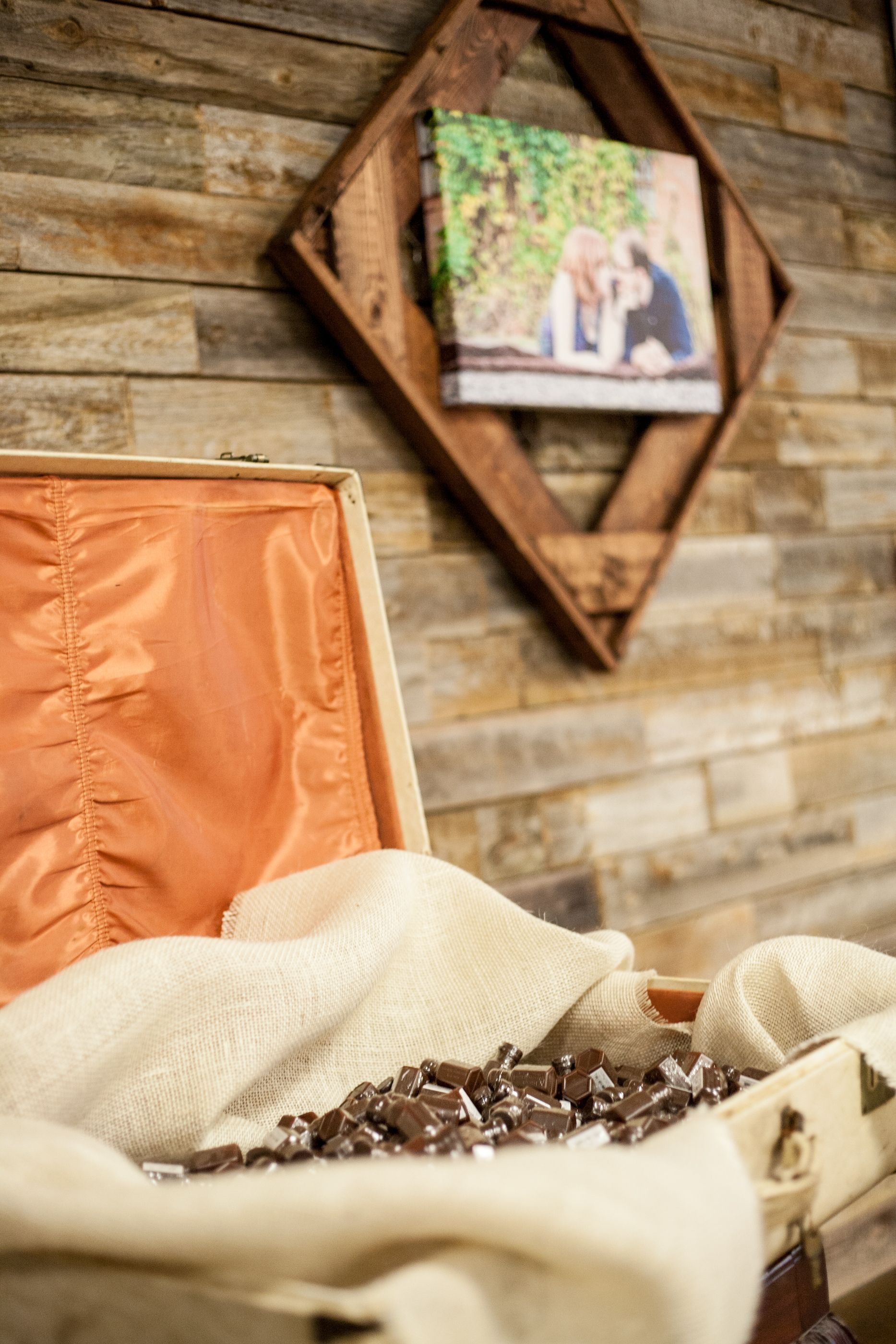 """""""Antique"""" suitcase with burlap drape holding Bubble bottles sitting by Photo wall"""