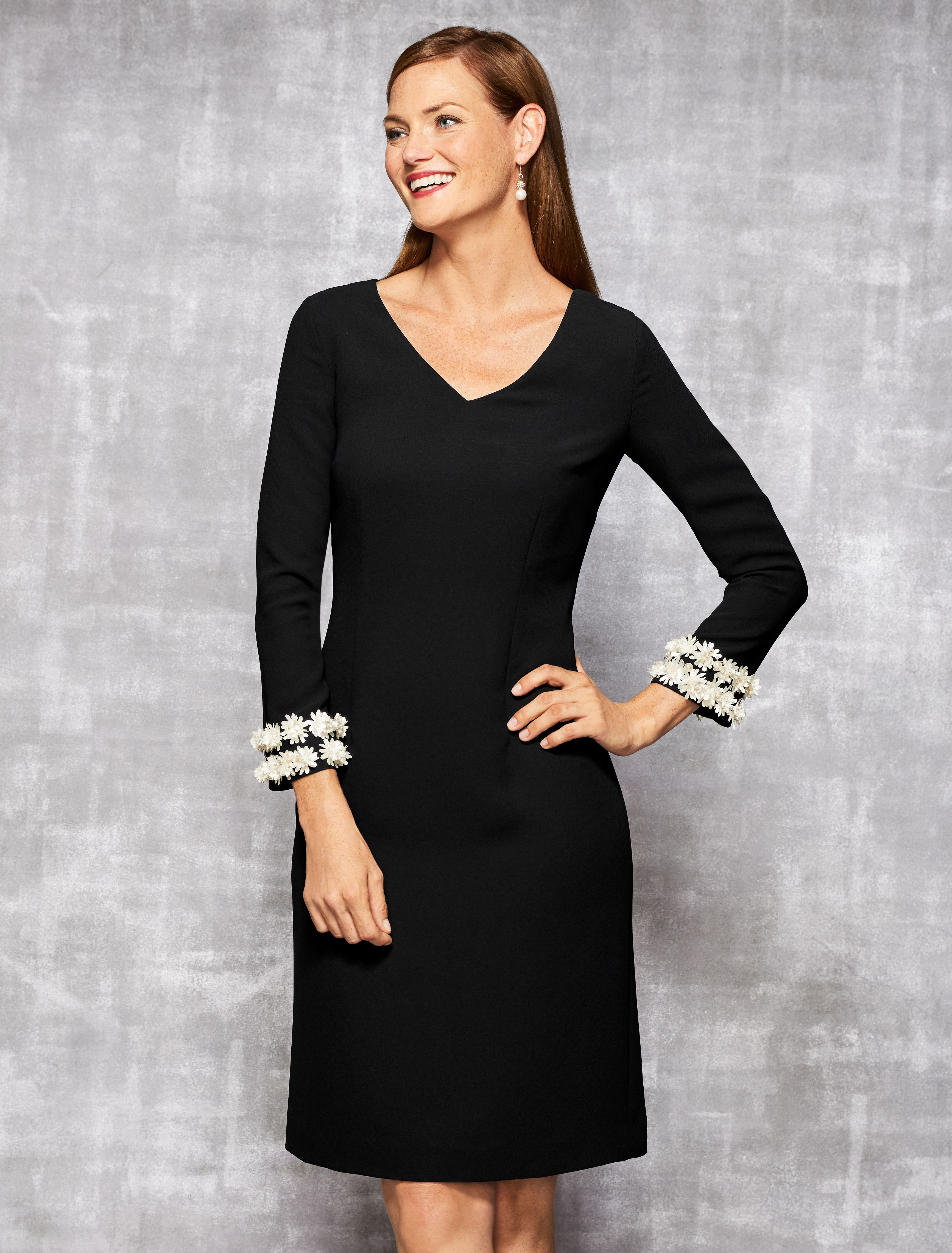 c2ea3f85a1f A little black dress with a twist. This sleek shift silhouette features  three-quarter sleeves embellished with delicate white flowers along the  cuff.