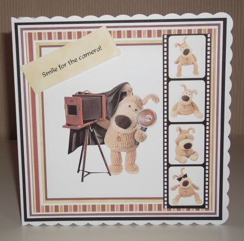 Boofle 'Camera Roll' Card  This lovely card is made from using layers of 250gsm black cardstock and 120gsm digitally printed papers.  The main image of the card features the very cute and loveable Boofle with his camera and flash.  The 'film strip' features additional images of Boofle and is raised slight from the card using foam pads, as is the main 'Smile for the camera!' sentiment.