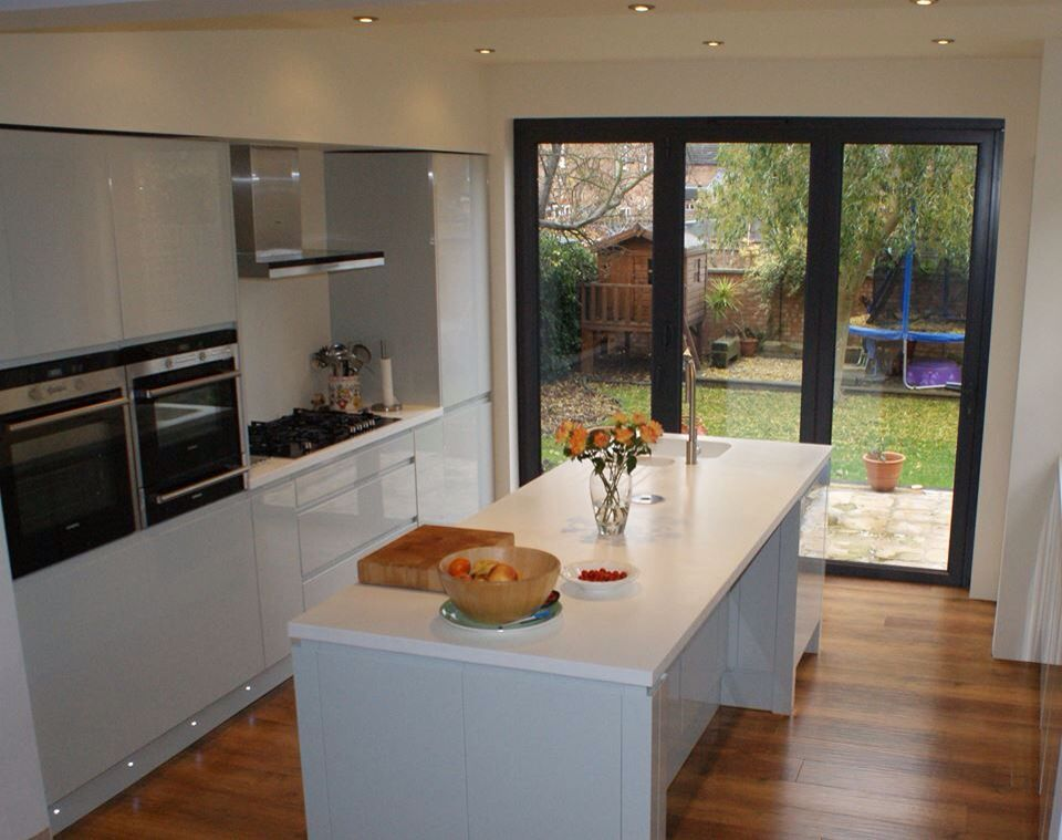 Sleek Welford handle less kitchen in grey gloss with an island. This ...