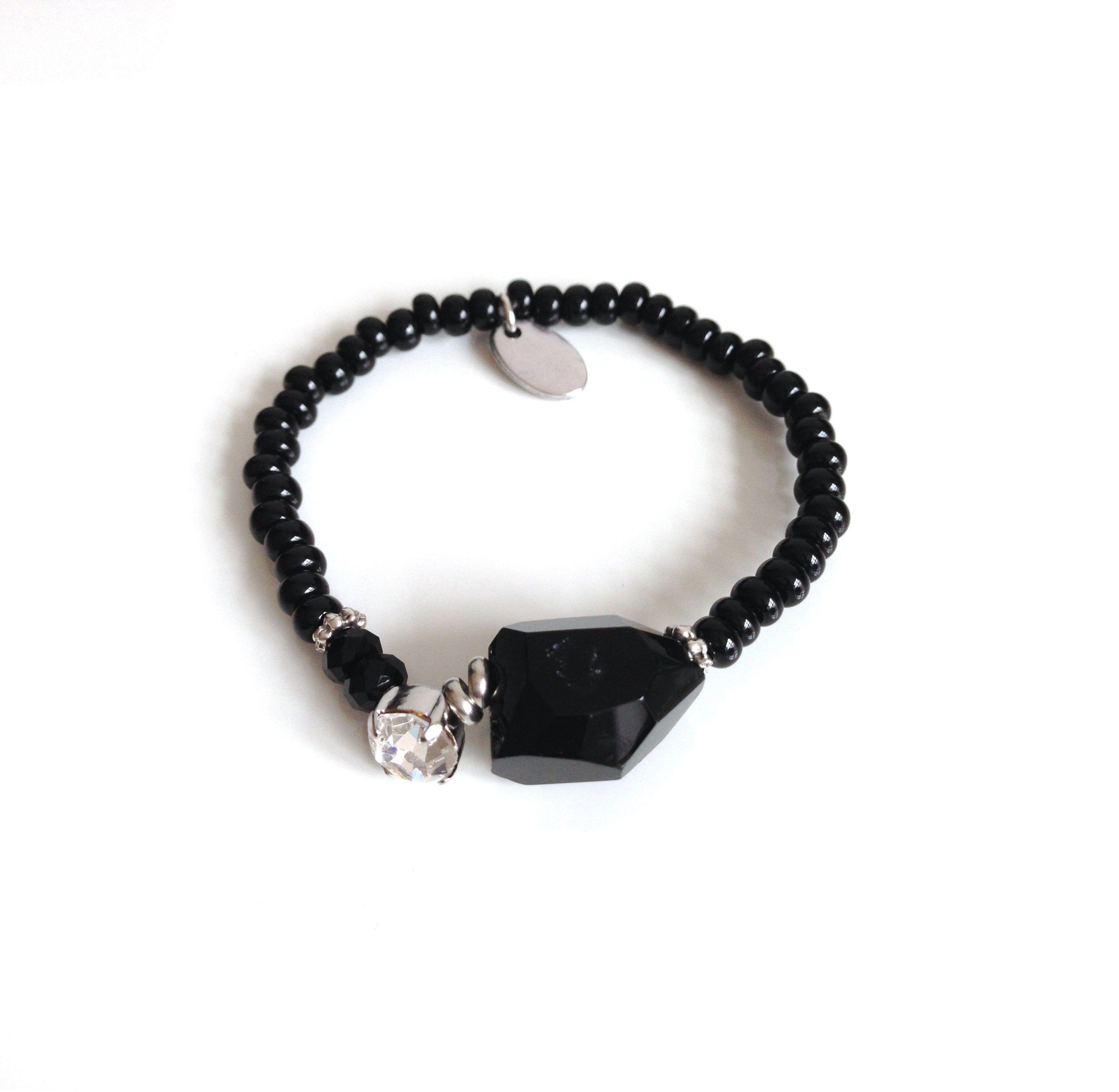 Elastische armband van zwarte rocailles(kleine kraaltjes die niet helemaal rond zijn),voorzien van een zwarte steen, een Swarovski steen, Bazou label enzilverkleurige accenten.Zie afbeelding.
