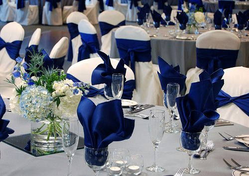 Royal Blue Napkins And Sashes Against White Chair Covers