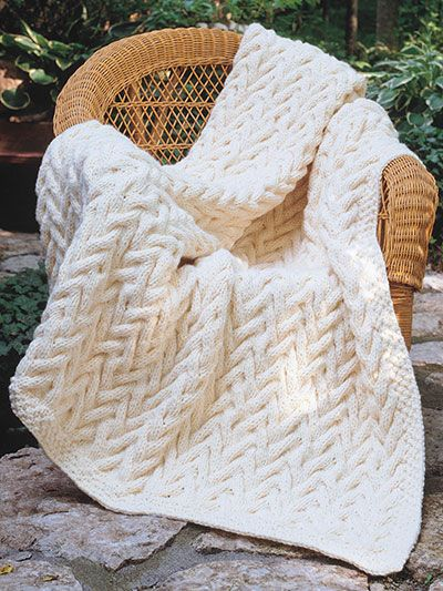 """The thick, warm fabric of this afghan makes it great for the den or cabin. The easy overall cable pattern gives the impression of complexity. Knit with 34 skeins of Plymouth Yarn Encore Chunky using U.S. size 15/10mm 32"""" circular needle. Finish..."""