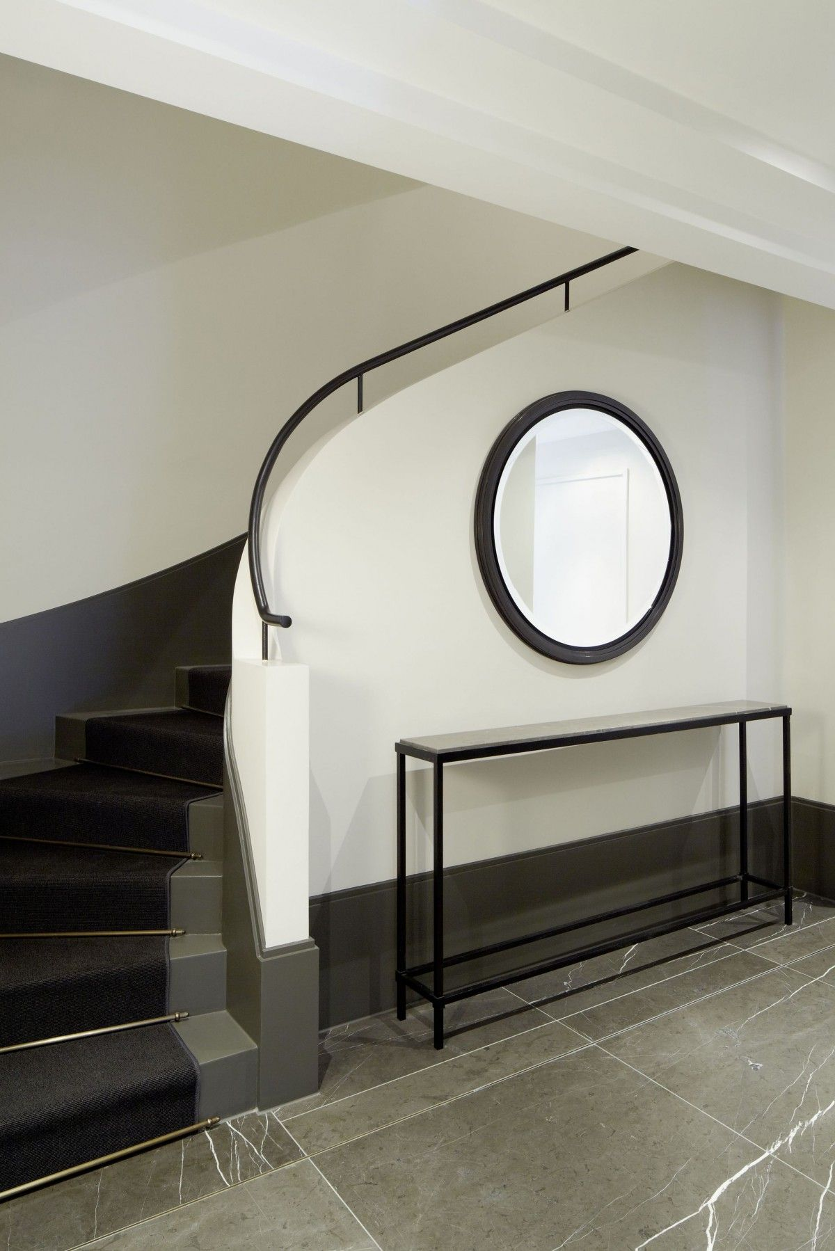die geschwungene treppe f hrt vom eingangsbreich der mit dunklen naturstein gefliest ist in. Black Bedroom Furniture Sets. Home Design Ideas