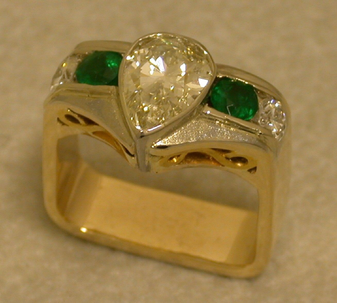 This hand fabricated ring has been crafted from 18kt. white & yellow gold. Set in the center is a 1.75ct. pear shaped diamond, bordered on either side are .50ct. emeralds.