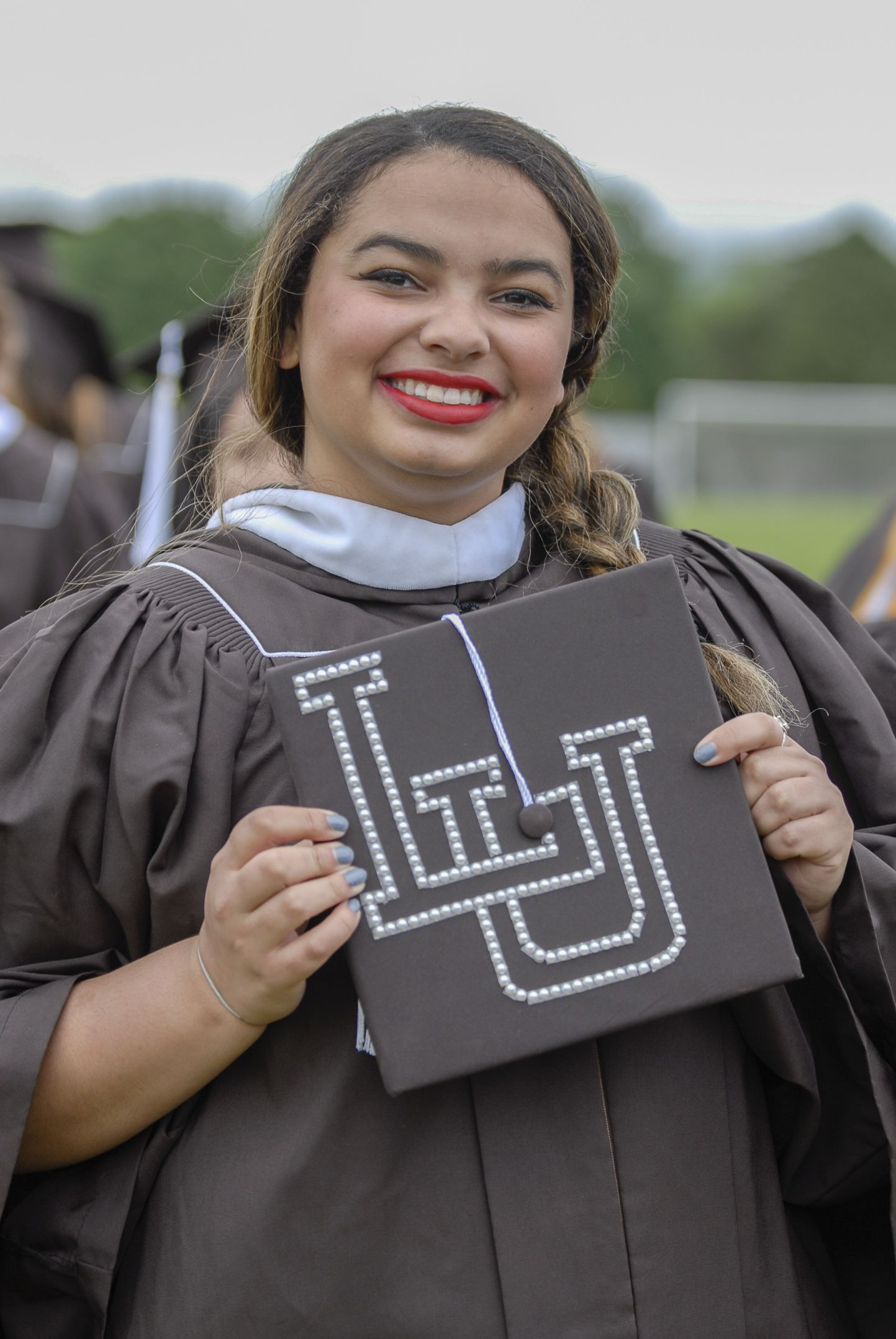 """Danielle Joy, '17, holds her graduation cap Monday, May 23, 2017, outside Goodman Stadium. Joy, an international relations graduate, decorated her hat with the letters """"LU"""" to show her Lehigh pride. (Roshan Giyanani/B"""