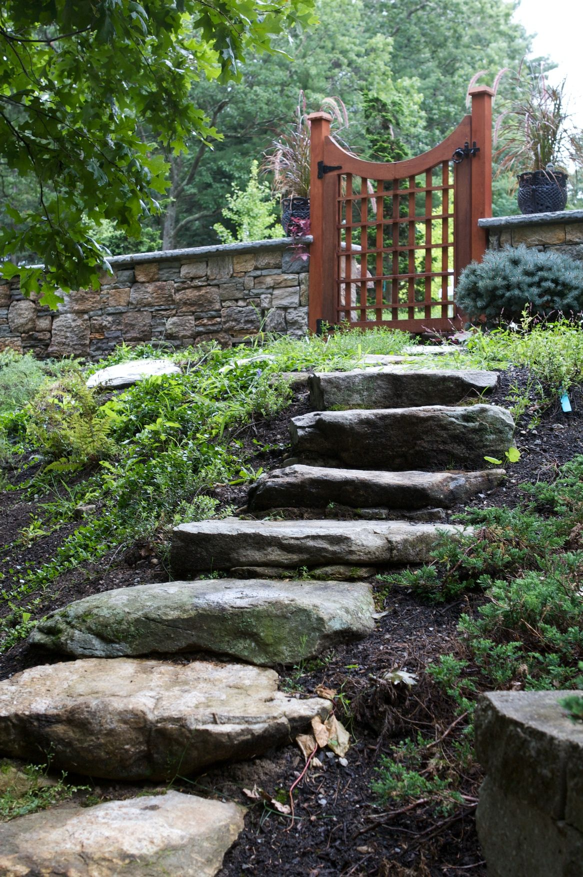 Natural stone slabs create a stairway to wooden gate gates