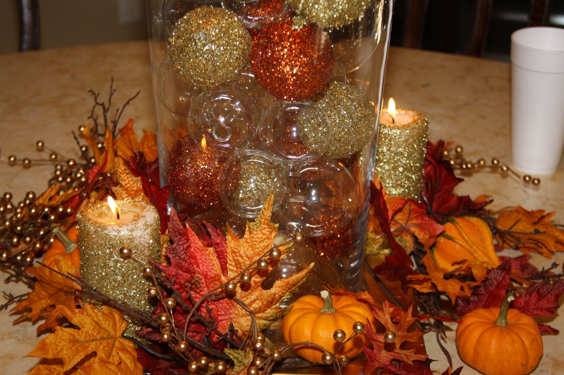 Thanksgiving Centerpieces made with clear cylinders filled with styrofoam balls we glittered ourselves and mixed in clear glass balls. Inexpensive candles sprayed with adhesive then rolled in same glitter we used on the balls!