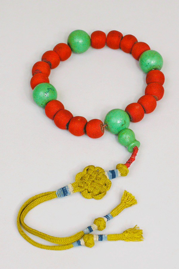 Pressed Medicine Prayer Beads China; early 20th century, 16 pressed medicine pellets wrapped in bright red silk is a distinctively Chinese string of beads that combines medicinal properties with aesthetic appeal. Its 3 green turquoise separator beads and a guru bead with a finely braided endless knot decoration add vivid colors to the brilliant red of the beads.