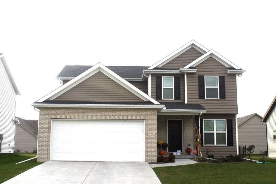 2 Story House With Dark Brown Siding White Trim Garage Door Tan Brick And Black Roof Raised Panel Shutters