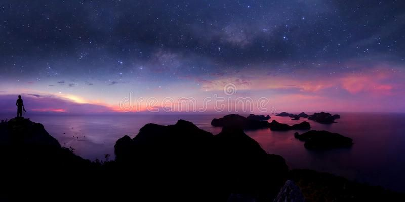 Man standing on the mountain with panorama view and million stars galaxy Purple