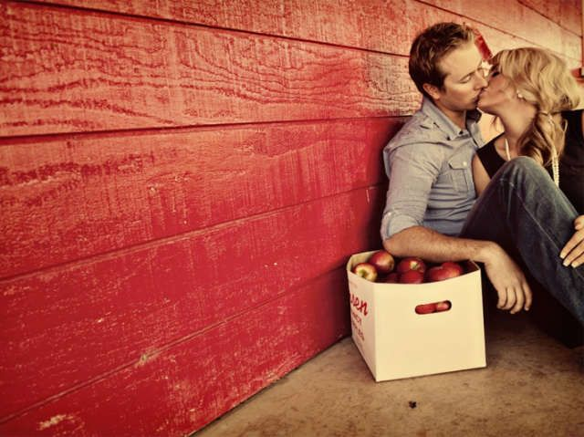 A couple share a kiss by a red wall and a box full of red apples.