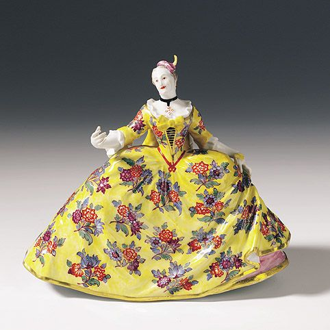Reifrockdame als Figurine. Weit ausladendes Kleid mit polychromen indianischen Blüten auf gelbem Fond. In der Linken pendelt ein Fächer. Auf dem Kopf ein keckes Federhütchen. Ungewöhnlich konstruierte Figurine, die auch einen Blick auf das Unterkleid und die fein modellierten Schuhe erlaubt. Kaendler-Modell. Blaue Schwertermarke Meissen, um 1740.