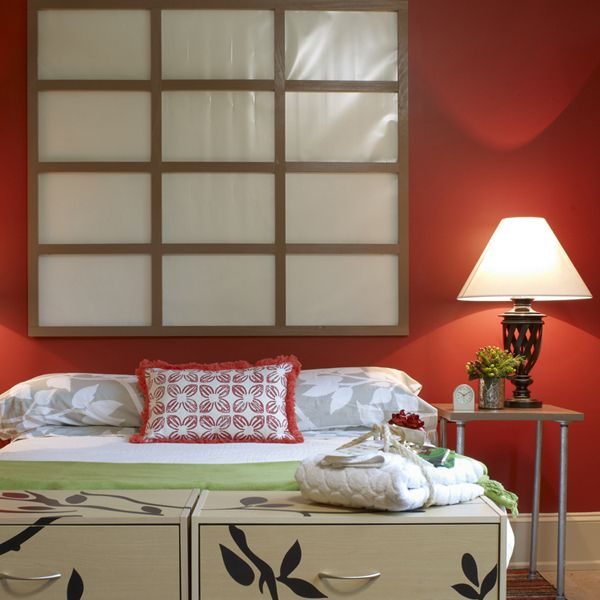 A shoji (paper screen) mounted to a vibrant red wall adds drama to the guest room.