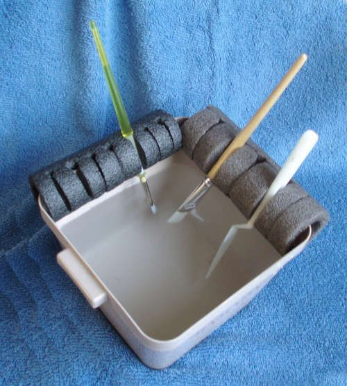 Paint Brush Holder - GREAT idea.  Cut foam pipe insulation to fit sides of container... and cut slits in foam.