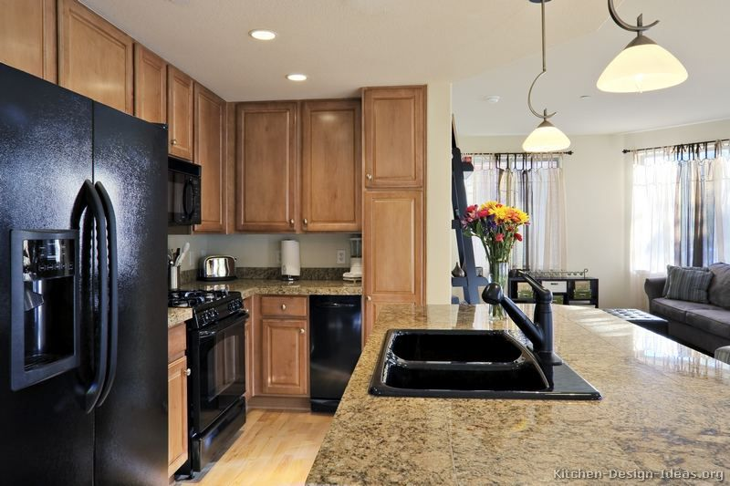 traditional light wood kitchen cabinets with black appliances
