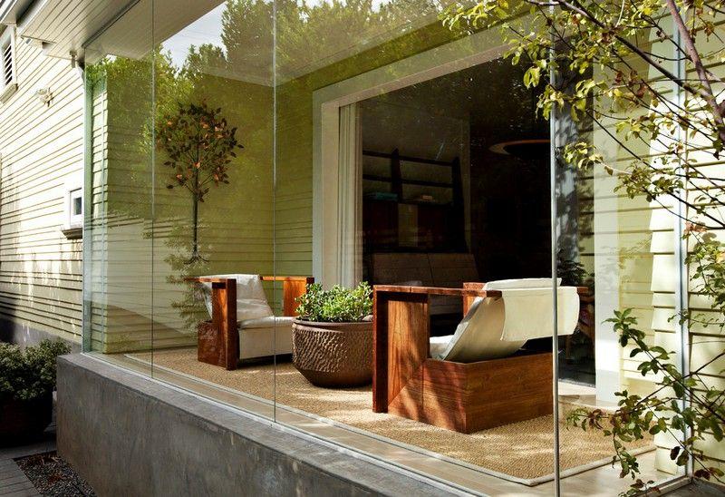 Kleiner Wintergarten mit Glaswänden und zwei bequemen Holzstühlen - tipps pflege pflanzen wintergarten