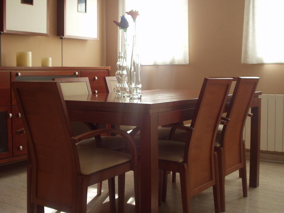Detalle de mesa con pata diagonal en madera de cedro con sillas