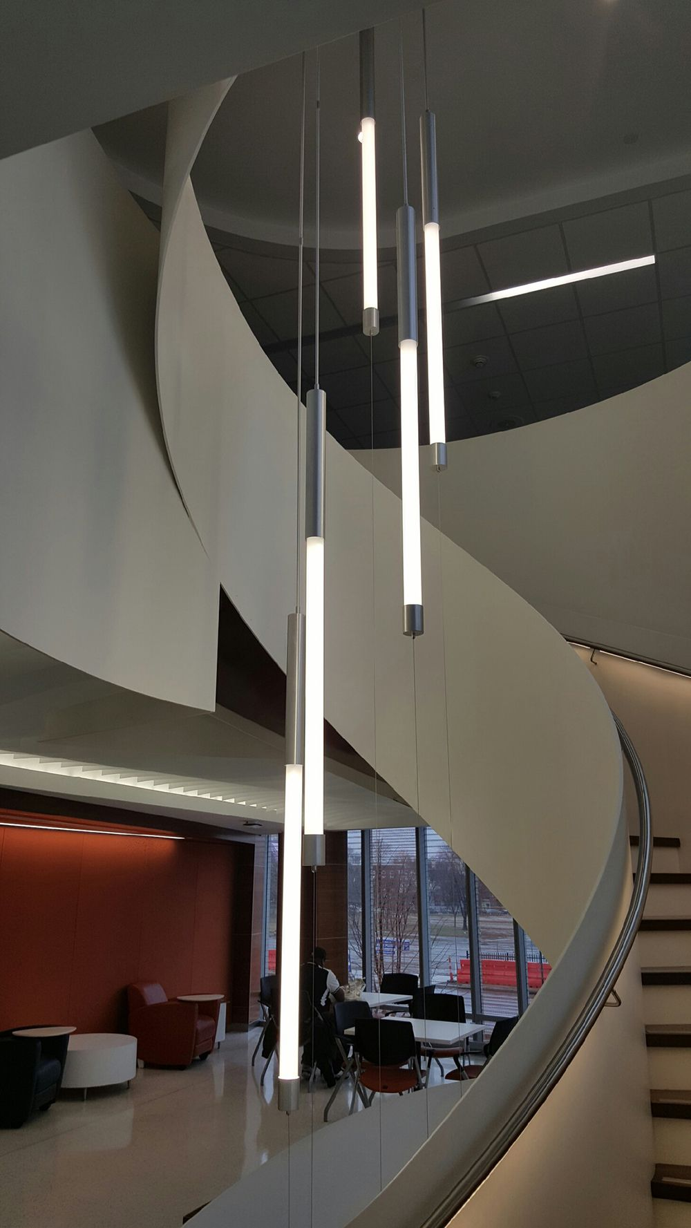 Delicate-looking Pavo 2.0 pendants by SPI Lighting are arranged in a configuration to decorate this stairway.