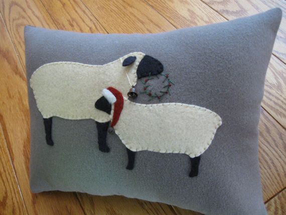 This one is another one for the sheep lovers! Ive designed this one myself and it features two sheep done in tea stained wool felt with black face and legs. The mom is holding an embroidered wreath and the smaller sheep is wearing his Christmas hat complete with furry trim and rusty jingle bell.  This pillow is completely hand stitched and is done on a medium brown colored wool. Ive stuffed it with polyester fiberfill. It measures 9 1/2 x 12 1/2 and comes from a pet and smoke free home.  I…
