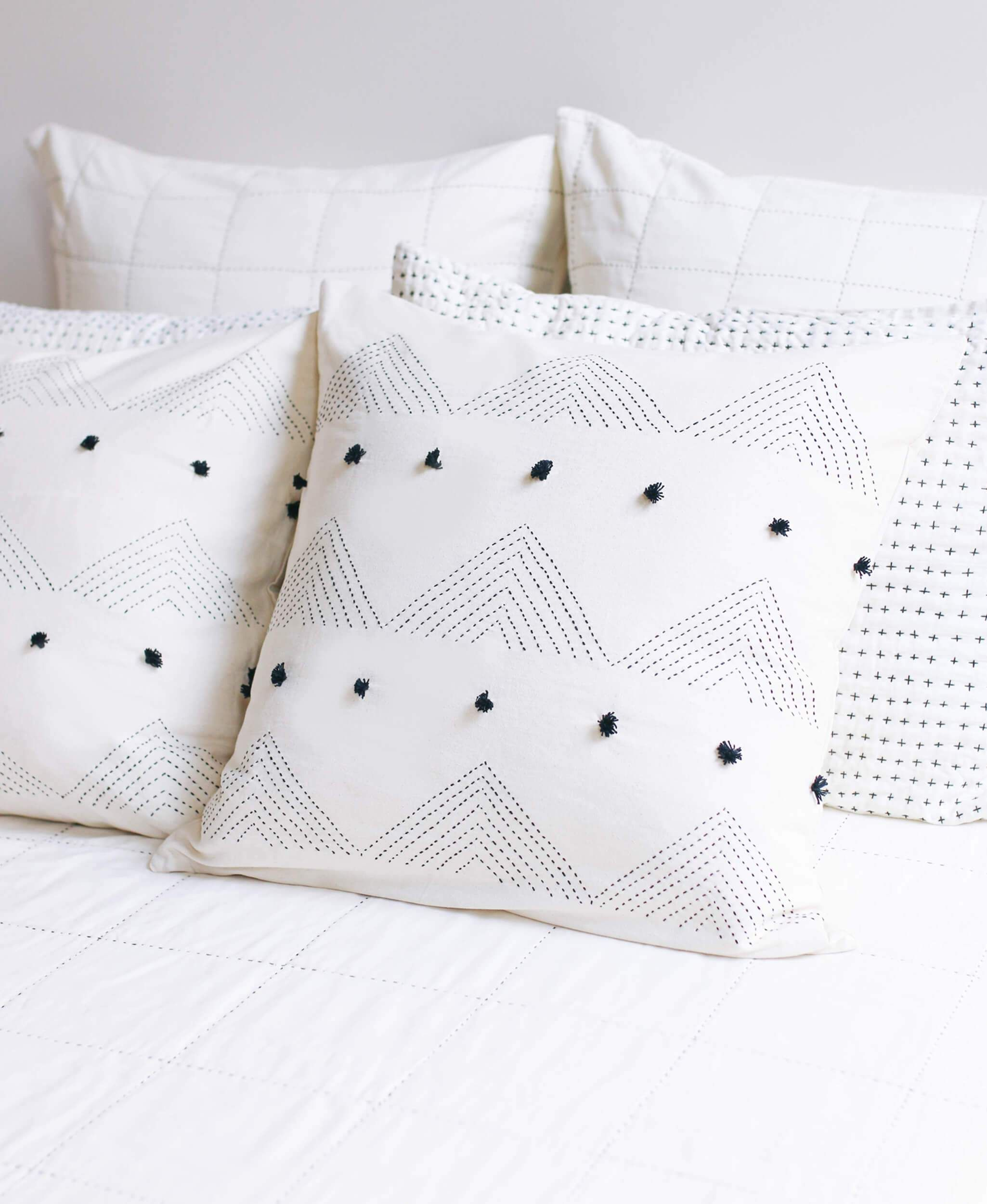 Add a touch of modern, global style to your home decor with this throw pillow. Its charming triangle stitch is enhanced by dynamic rows of playful pom poms. Pair it with other decorative pillows to create a one-of-a-kind mix for a bed or sofa. PRODUCT DETAILS: Size: 22