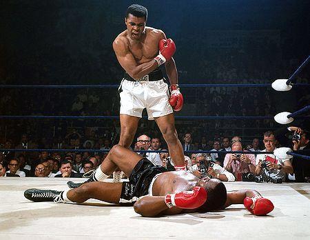 Muhammad Ali noquea en el primer asalto a Sonny Liston en su segundo combate (1965). Primera pelea de Ali bajo ese nombre al cambiar de religión. Su nombre de pila es Cassius Marcellus Clay. Es la fotografía más emblemática del boxeo.