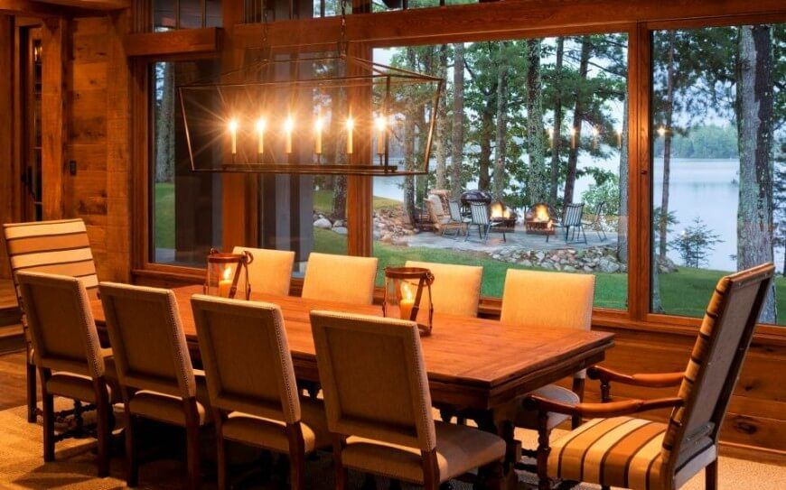 The Dining Room Is Lit Up At Night By Large Lantern Style Light Fixture Above Table And Two Candles In Jars On
