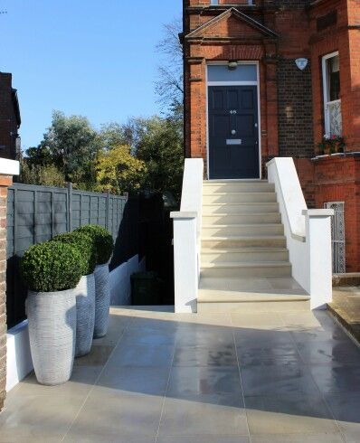 Sawn Indian sandstone steps and paving with Buxus balls in tall pots