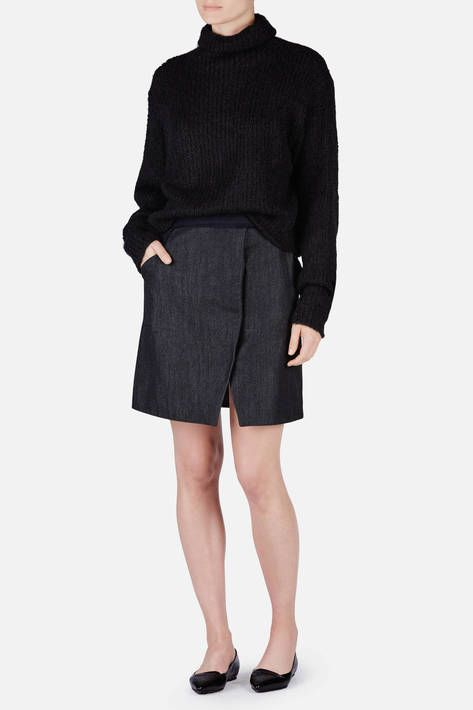 """The fall 2015 collection of Paris-based Coperni emerged from """"an exploration of round shapes,"""" explains co-designer Sébastien Meyer. That play of curves is subtle but striking in this wrap-style skirt. Made in France of a charcoal-hued blend of cotton and wool, the tailored silhouette has inset side pockets that accent the gentle curve of the centrally placed front slit and the circular form of the brushed metal snap closure."""
