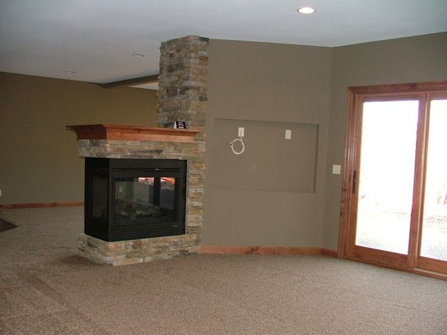 3 Sided Stone Fireplace With Wood Mantle With Adjacent Tv