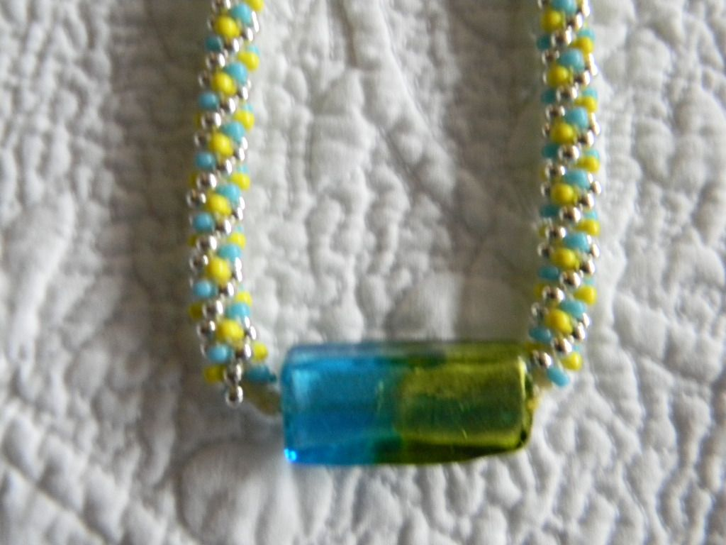 """Turquoise, yellow and silver glass beads have been hand woven into a lovely necklace of approx.21"""" including the silver tone magnetic clasp. The focal bead is a rectangle glass bead.The colors of the bead are Turquoise and Yellow and coordinate ..."""