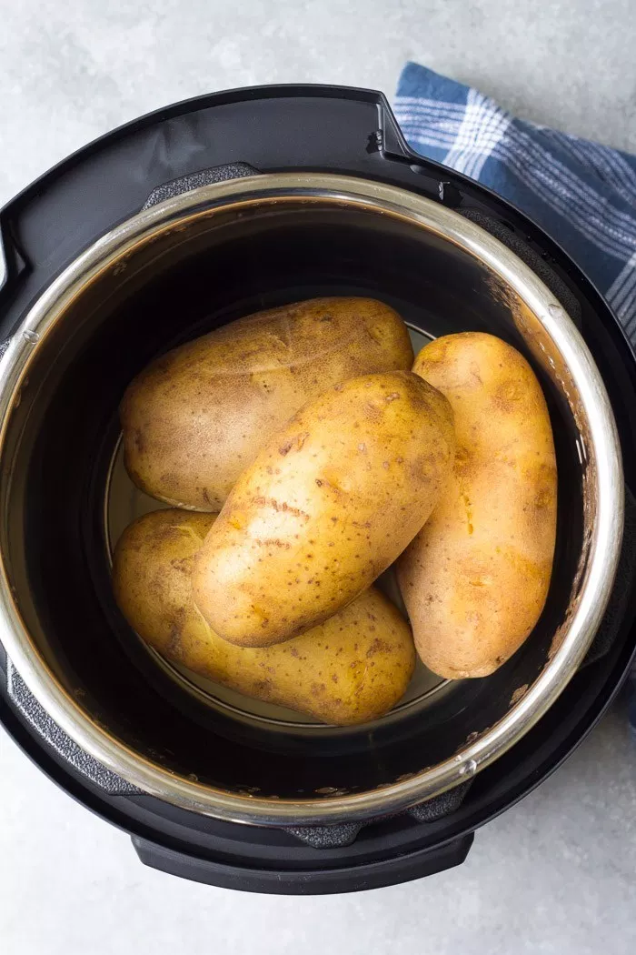 A foolproof recipe for easy Instant Pot Baked Potatoes! Learn how to cook the best baked potatoes in your pressure cooker, plus how to make baked potatoes with crispy skins. When pressure cooking potatoes, the size matters: post gives cook time for small, medium and large russet potatoes. This is one of my favorite Instant Pot recipes for quick meals! #russetpotatorecipes