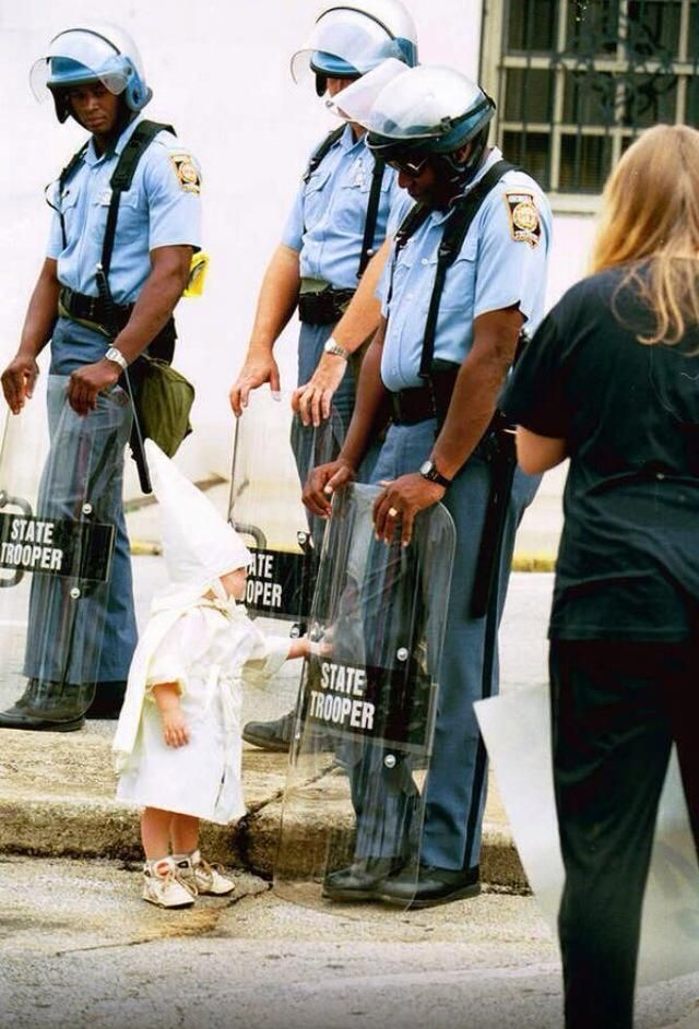 Have a picture of a baby Klu Klux Klan member watching himself in the riot shield of a black state trooper.