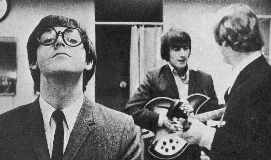 Paul goofing off with glasses, with John and George