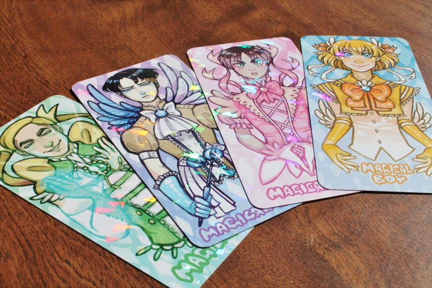 "All 4 shiny, holographic bookmarks featuring Attack on Titan characters as Magical Boys~!  color front (prism coating)  greyscale back (matte coating)  2.75"" x 6"" (7cm by 15cm)  rounded corners  300 gram paper  Available individually in our shop as well!"