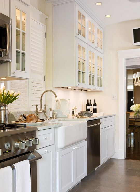 Marble counters and a limestone tile floor give the small kitchen a sophisticated yet hardworking feel. - Traditional Home ® / Photo: Gordon Beall / Design: Paul Corrie