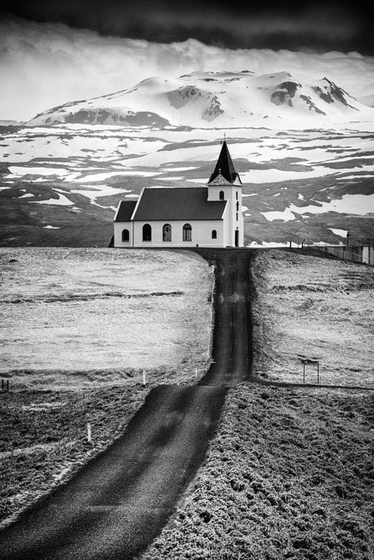 Church and mountains in iceland art print for sale road leading to ingjaldsholl church snaefellsnes iceland black and white image with stark contrast