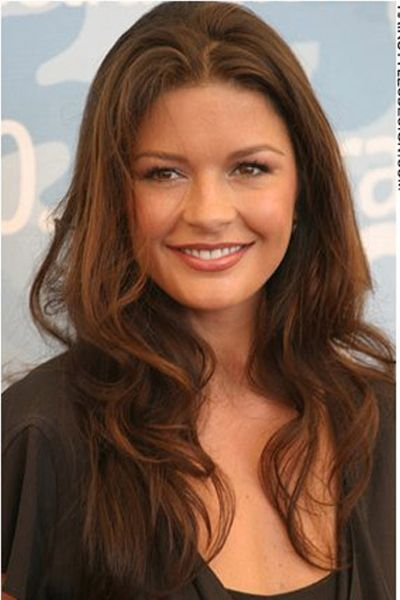 For this hairstyle, Catherine Zeta Jones has her hair long with a slight wave to it. It is parted in the center with the hair falling evenly all around. This conservative style is chic and classy.The hair is cut long.A warm hair colour such as this auburn shade, looks great.
