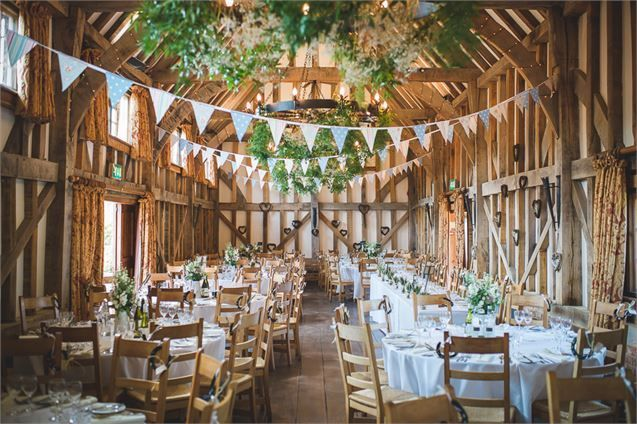 A Wooden Beamed Wedding Venue With Bunting Greenery And Fairy Lights