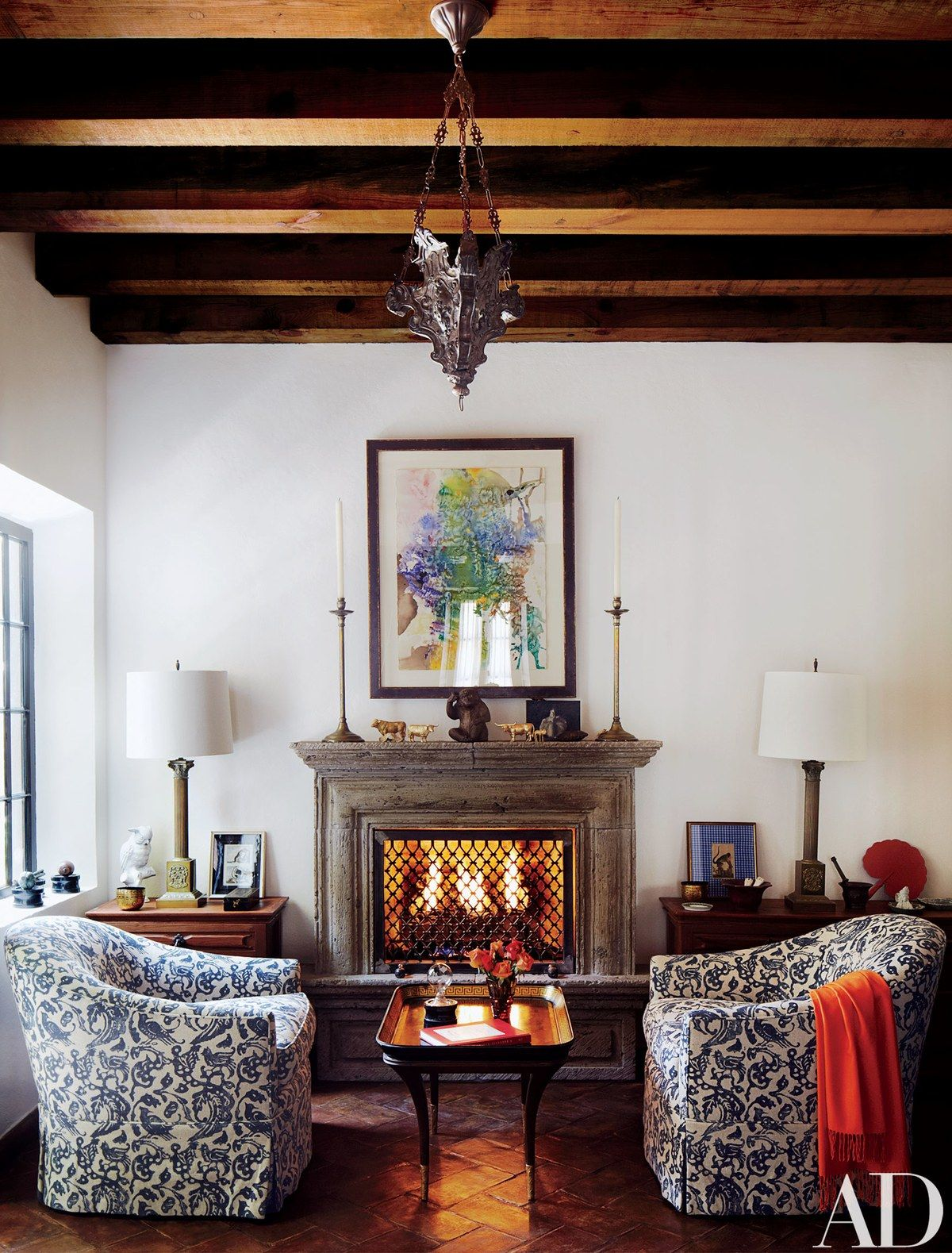 a watercolor by fisher hangs over the fireplace in the breakfast